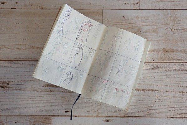 百均浪漫◆セリア BLANK NOTE クラフト A6 120枚 しおりひも付。子どもたち、何やら漫画を描いています。
